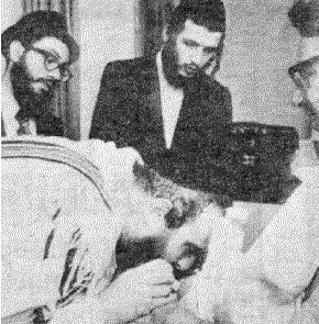 Rabbi bent over baby, sucking blood from circumcision wound