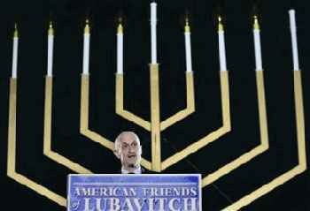 "Chertoff, with huge menorah behind him; ""American Friends of Lubavitch"""